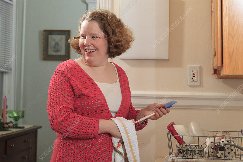 Young woman with Autism drying dishes