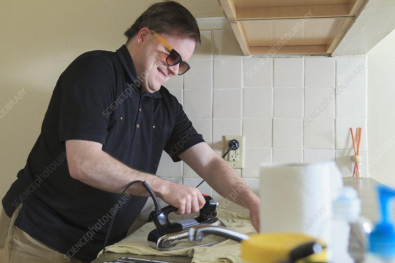 Blind man ironing his shirt at home