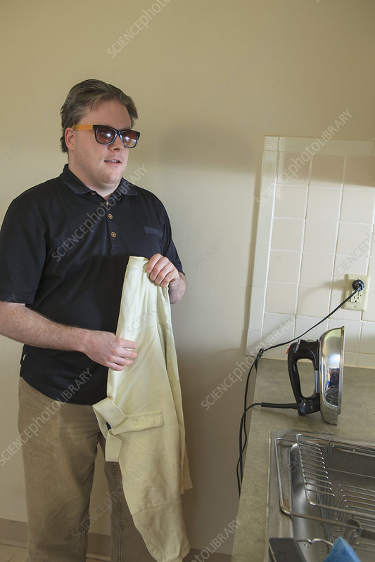 Blind man ironing his shirt at home