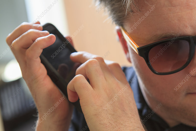 Blind man using his cell phone