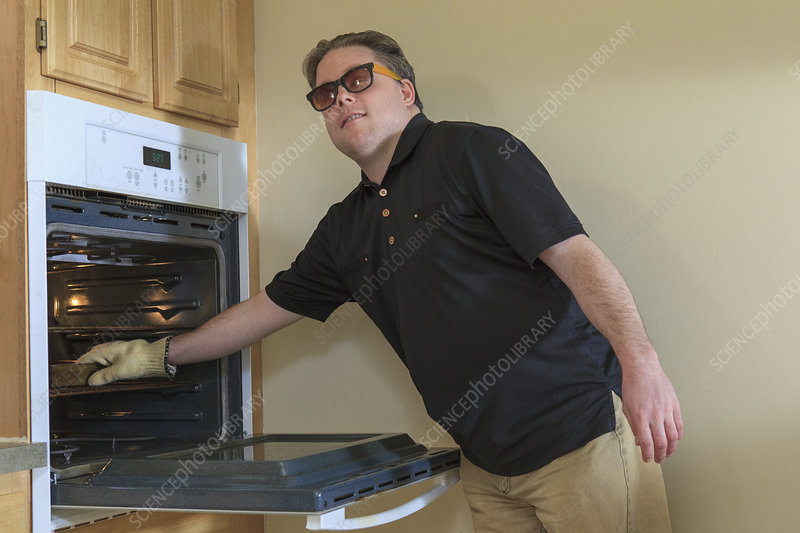 Blind man using the oven