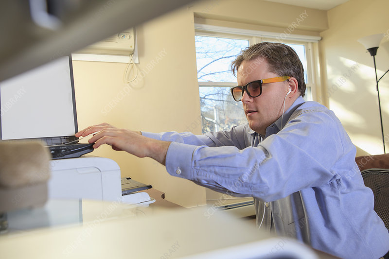 Blind man scanning paperwork at computer