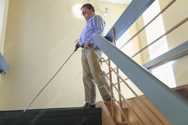Blind man using his cane on the stairs