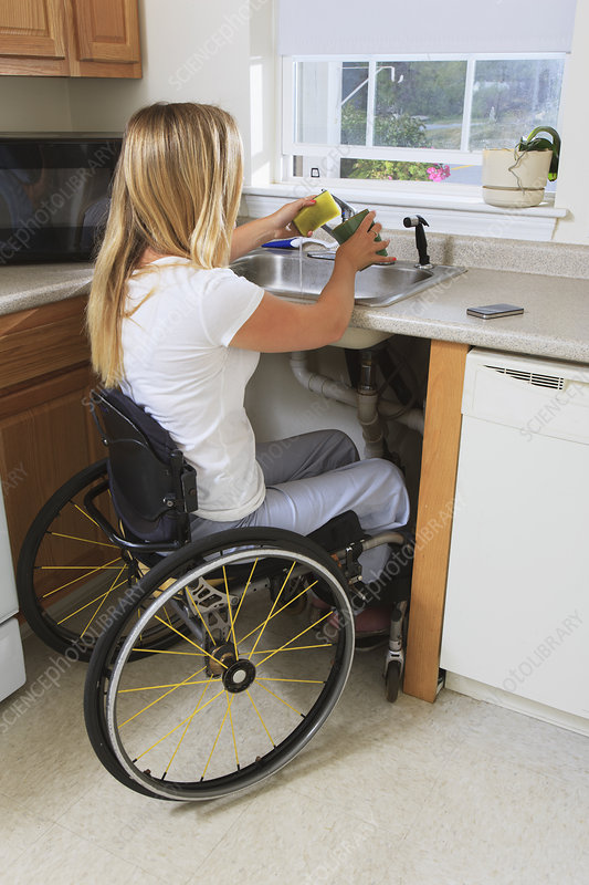 Woman with spinal cord injury in kitchen