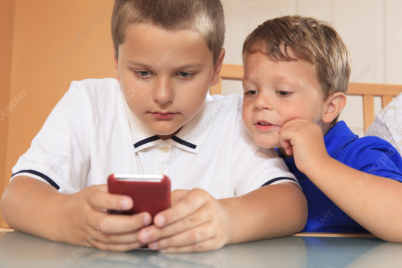 Young boys playing with their cell phone