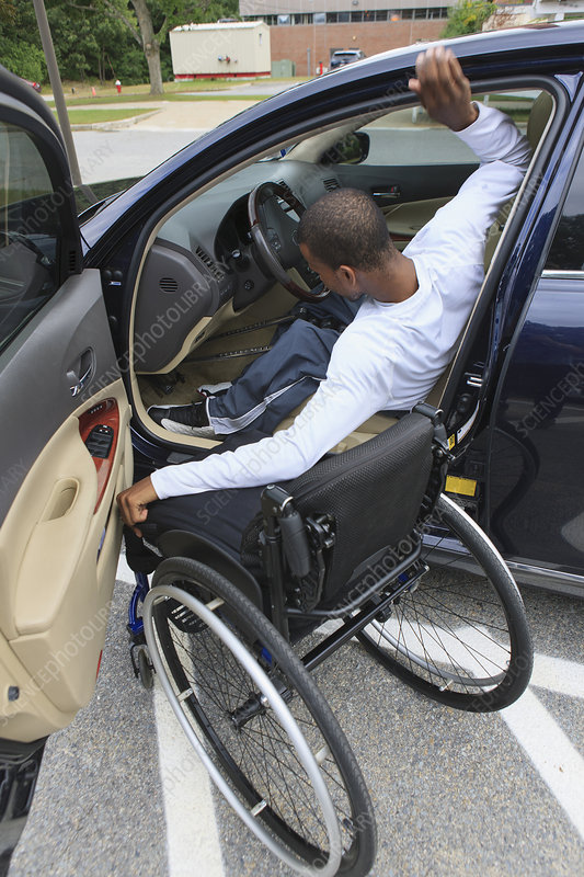 Man entering his car with his wheelchair
