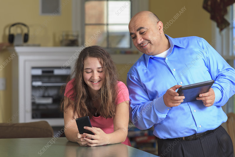 Father looking while daughter is texting