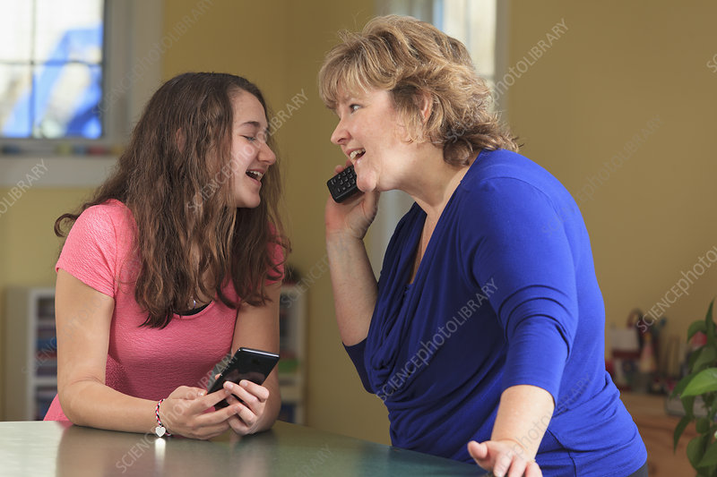 Mother and daughter using their phones
