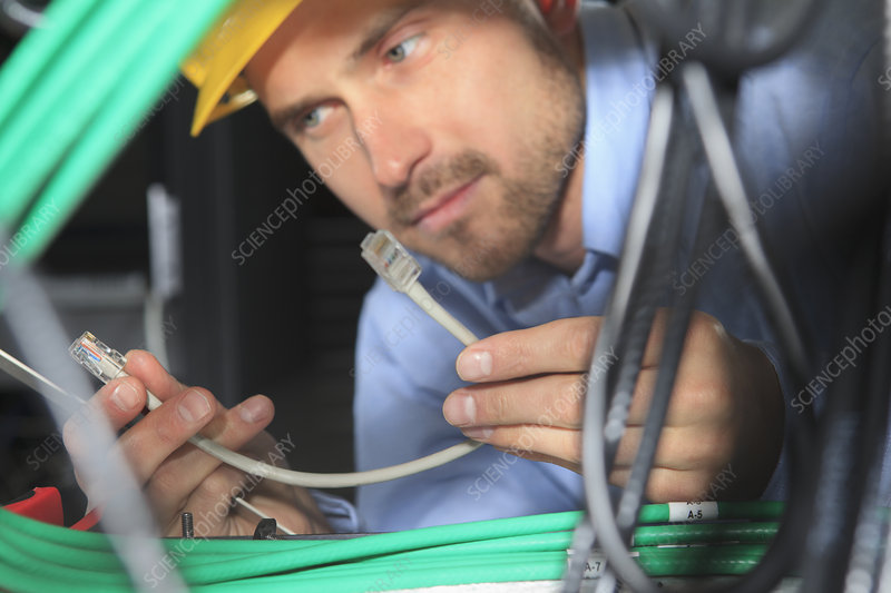 Network engineer examining patch cable