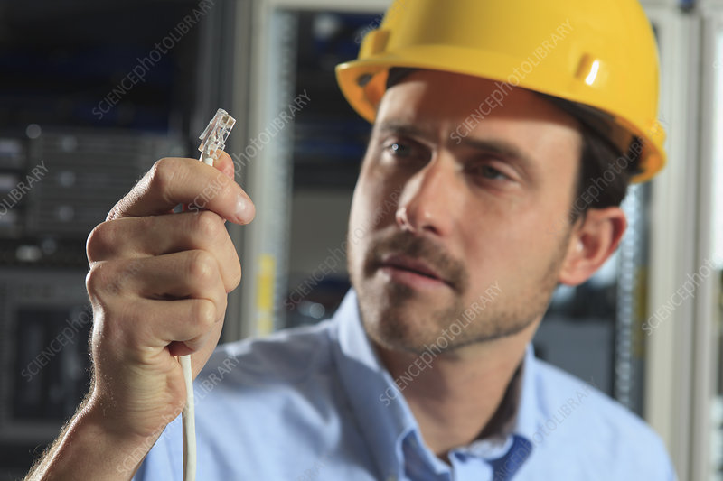 Network engineer examining cable crimp