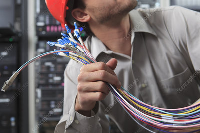 Network engineer preparing fiber cables