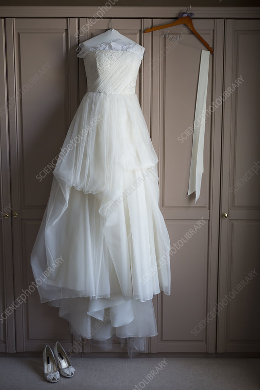 Wedding dress hanging and wedding shoes