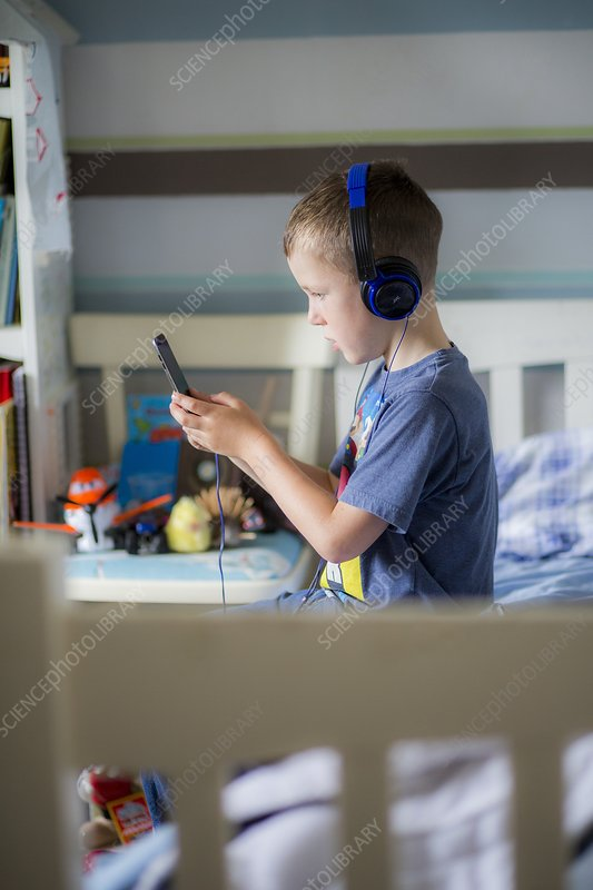 Boy wearing headphones using device