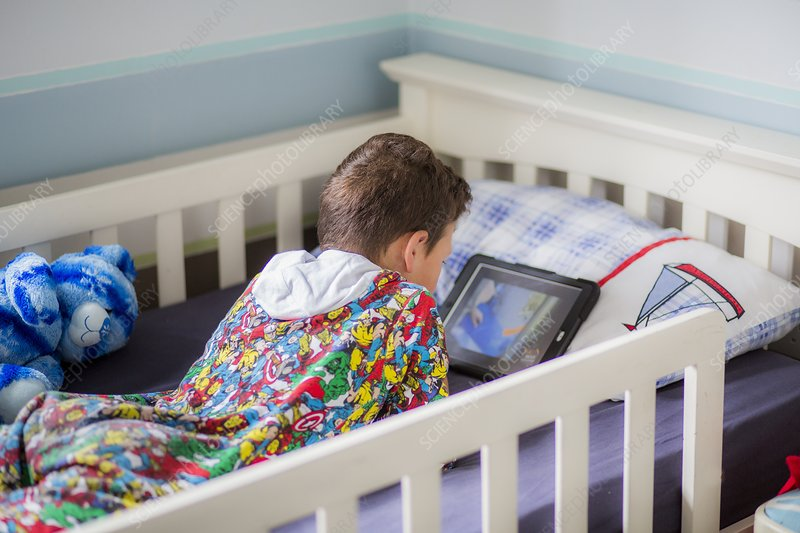 Boy in bed using a digital tablet