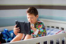 Boy sitting in bed using a digital tablet
