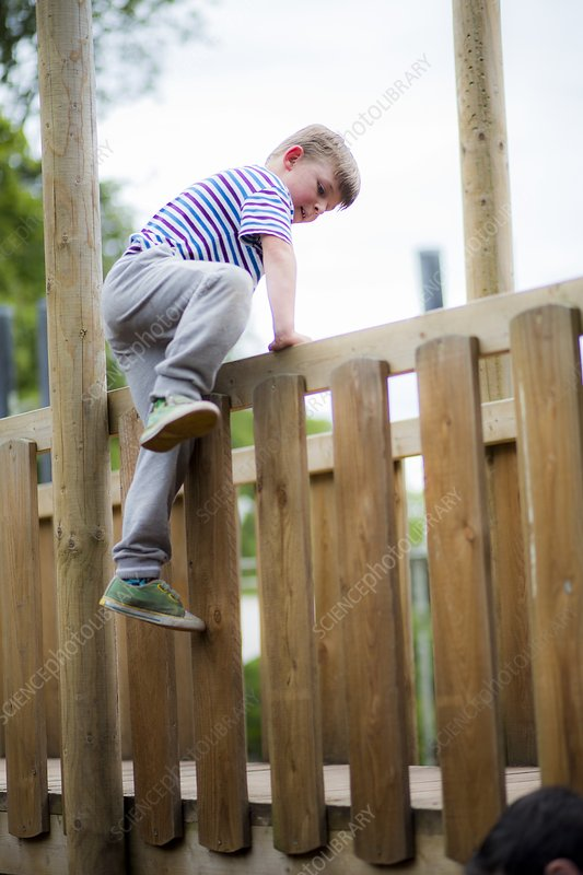 Boy climbing over wooden fence