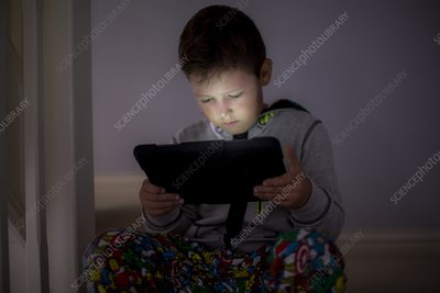 Boy using a digital tablet in the dark