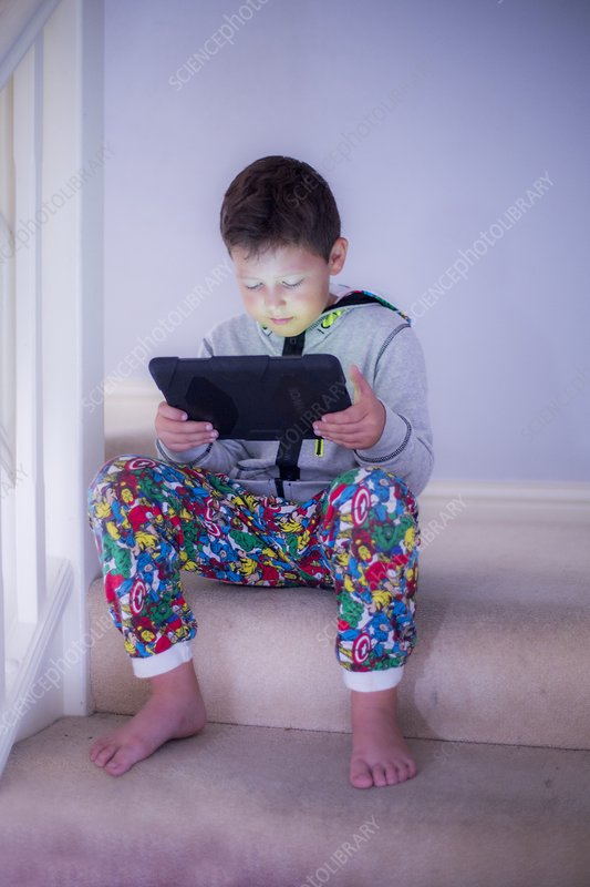 Boy sitting on a step using a tablet