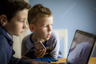 Boys using smartphone and laptop