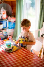 Young boy setting the table at home