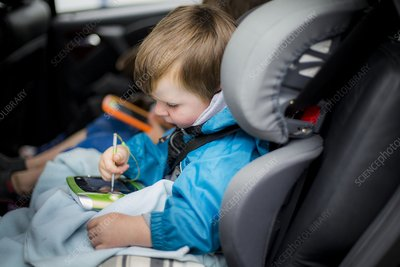 Boy in car using digital device