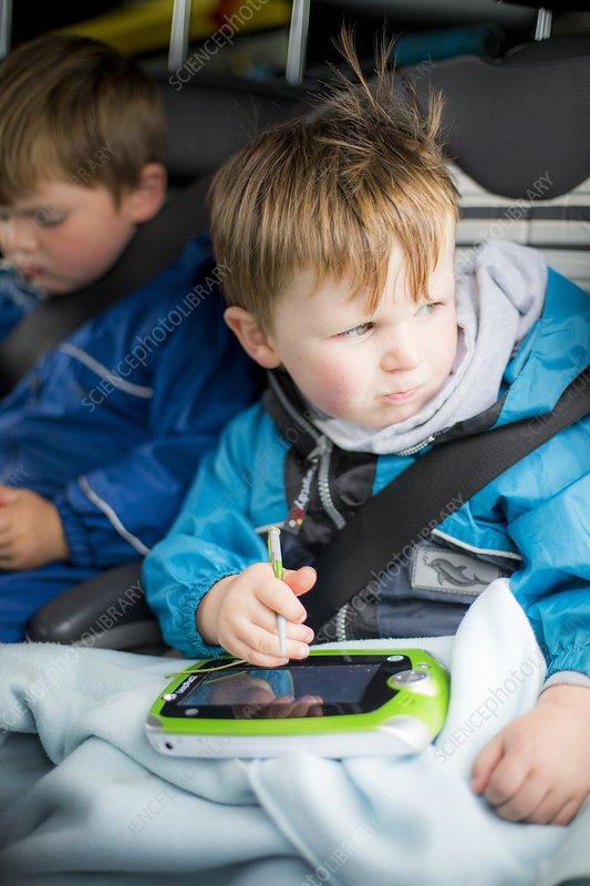 Boy in car with a digital device