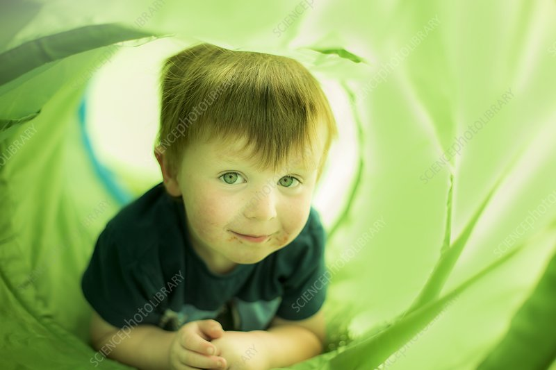 Boy in green tunnel