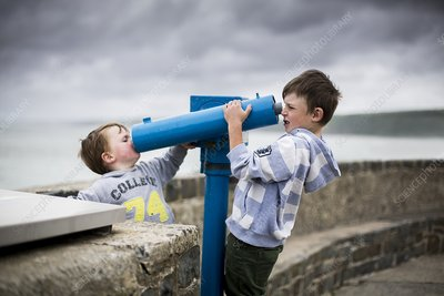 Boys using coin operated telescopes