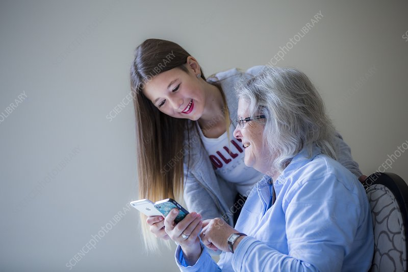 Girl showing grandmother smartphone