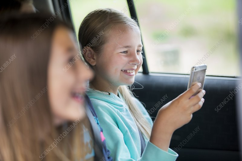 Girl using smartphone in car