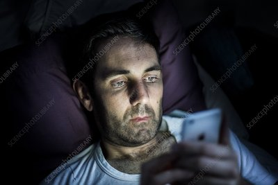 Man using smartphone in dark
