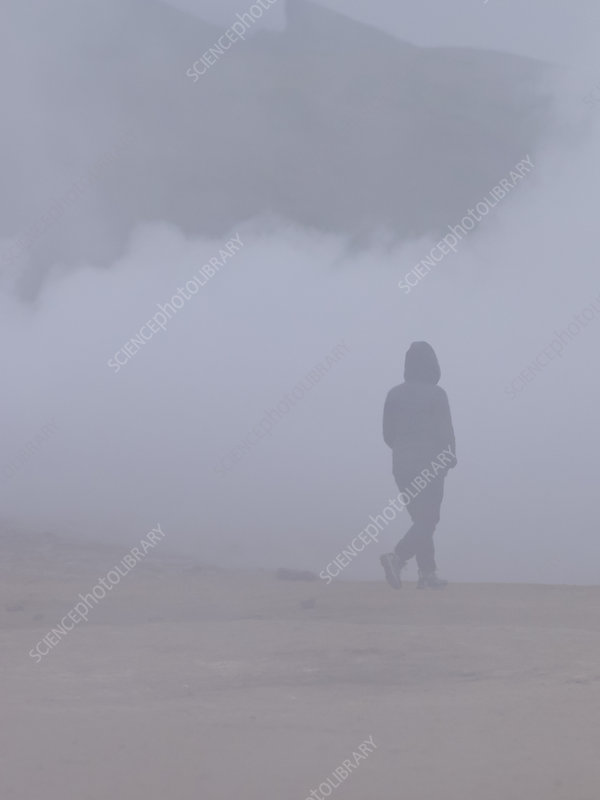 A person walking by hot springs