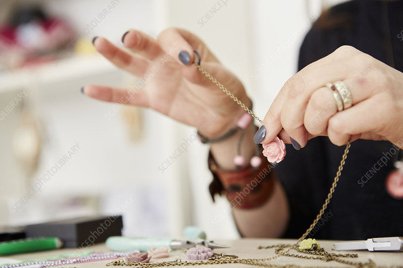 A woman holding a gold chain, and tools