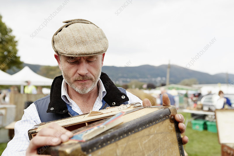 Man looking at a vintage suitcase