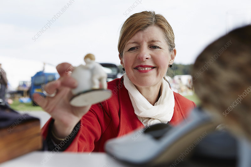 A mature woman holding a figurine