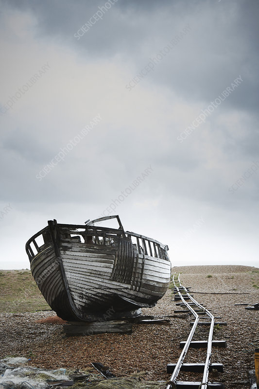 Abandoned wooden boat on the shingle