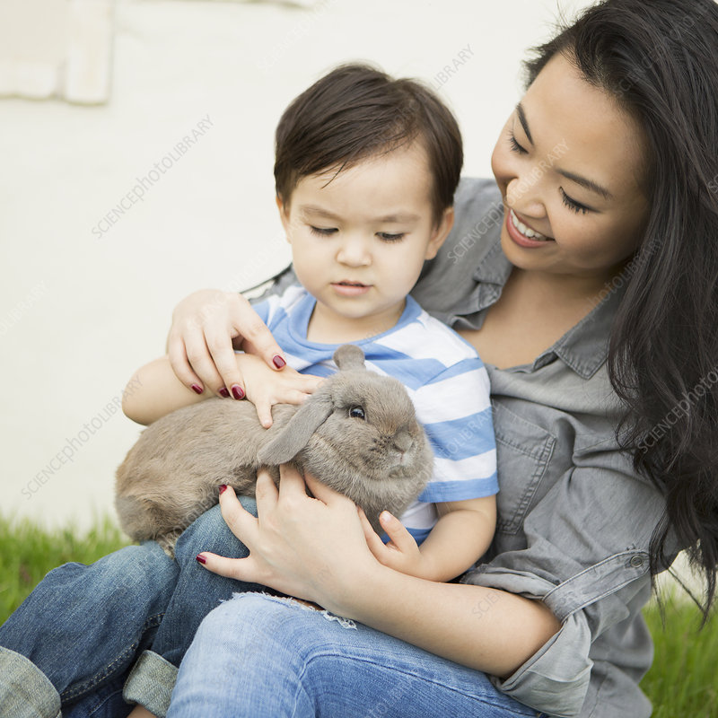 Smiling woman and child holding a rabbit