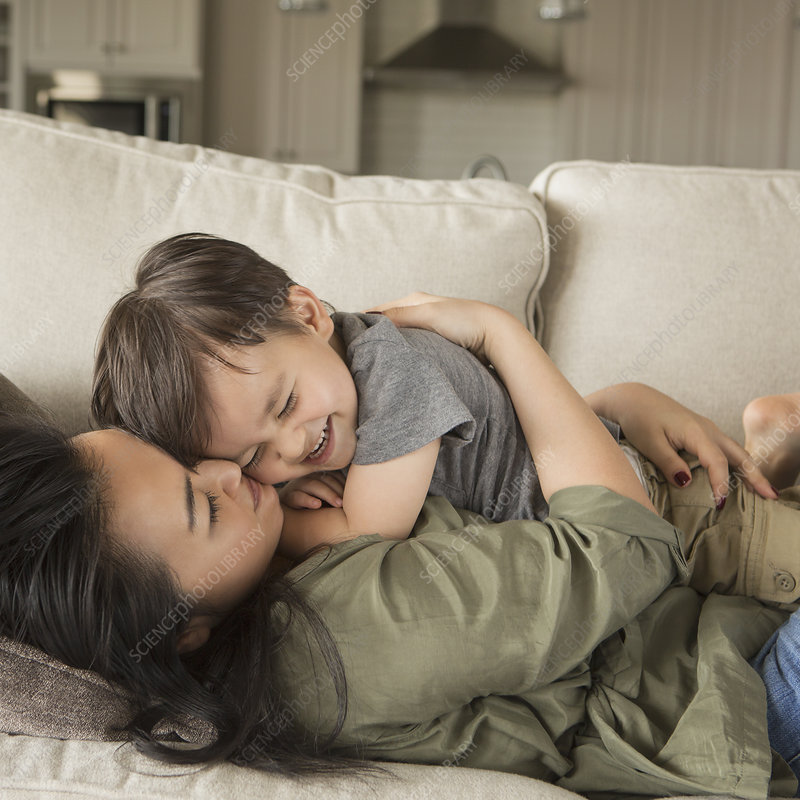 A woman on sofa cuddling her young son