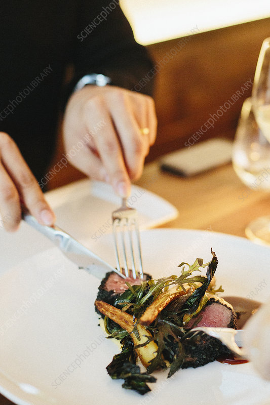 A man using a knife and fork eating meat