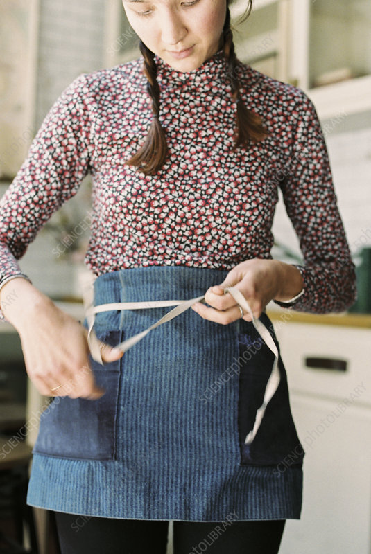 A woman tying the tapes of an apron