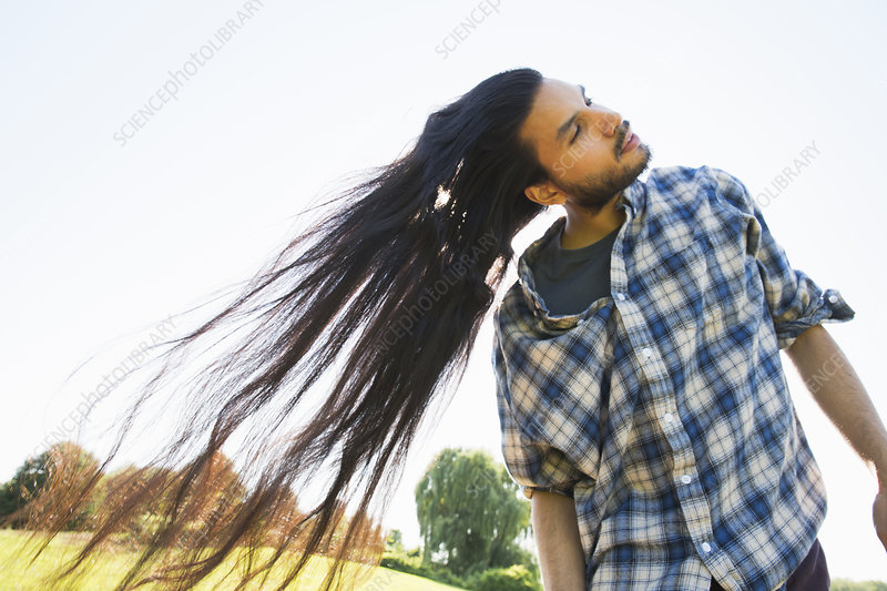 A young man shaking long hair