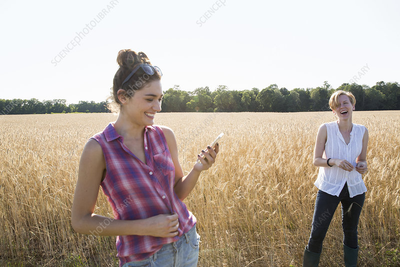 Two women one holding mobile phone