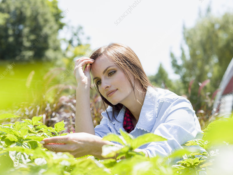 A young woman standing by racks of plants