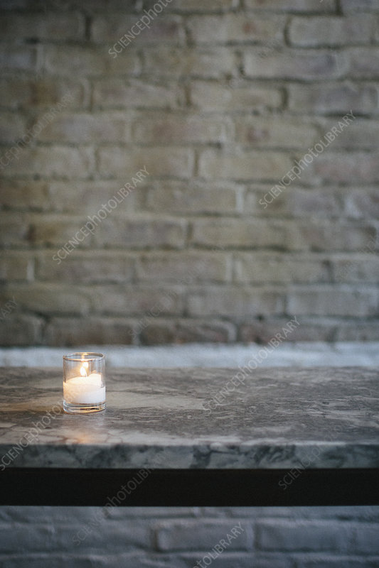 Lit candle on a marble bench