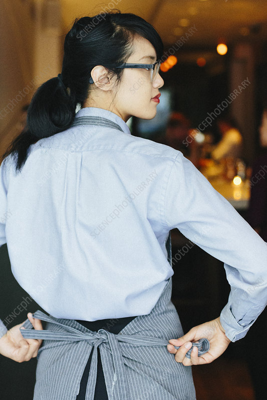 Waitress tying her apron around waist