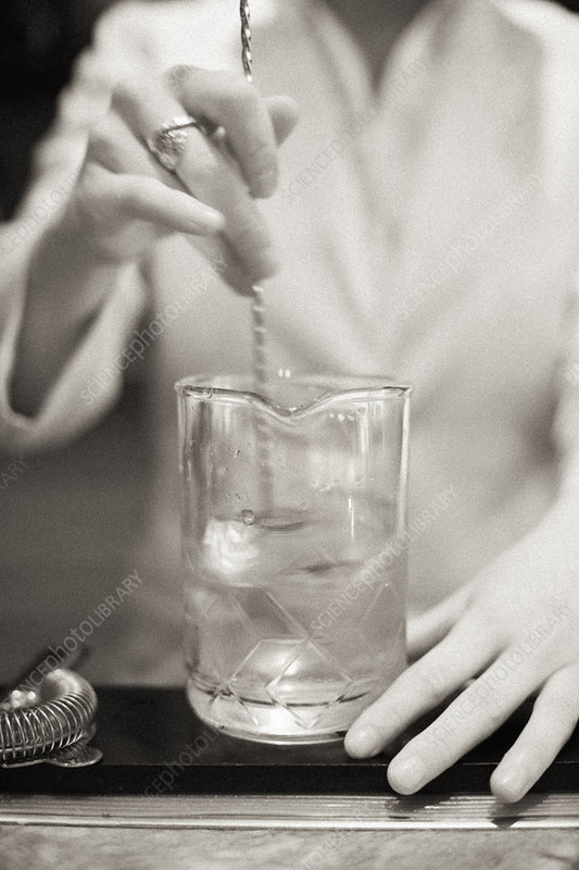 A young woman mixing a cocktail