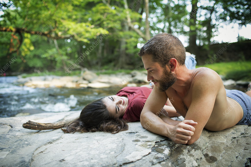 A young man and woman on rocks by river