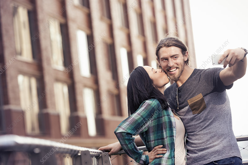 A woman kissing a man posing for a selfie