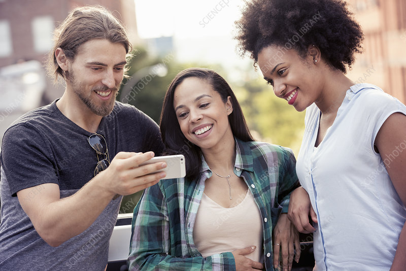 Three people looking at a smart phone