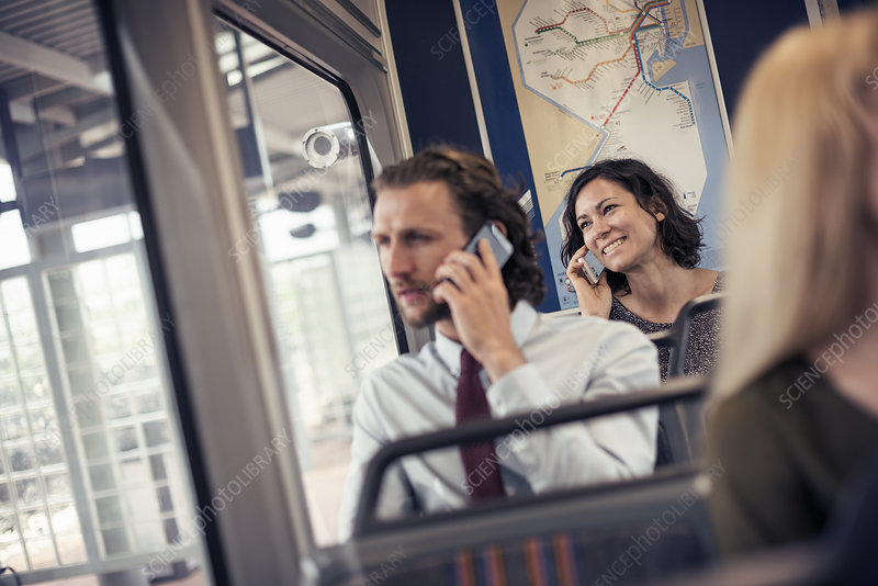 Two people on a bus talking on phones
